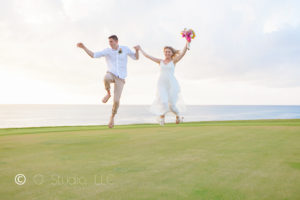 Seated Portrait of Buccaneer bride and groom on hole three jumping in the air